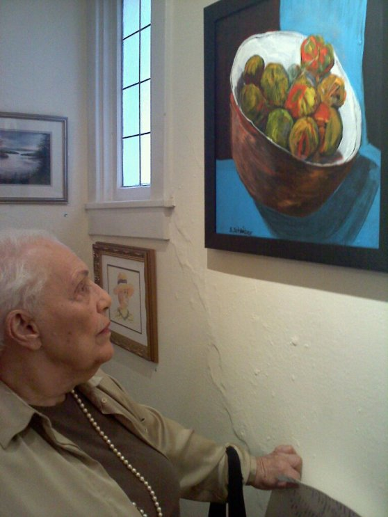 My mom with one of her still life paintings at an exhibit.